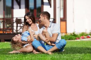 Junge Familie lacht auf der Wiese hinter ihrem Haus