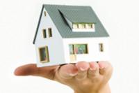 Bild zeigt offene Hand mit Modellhaus