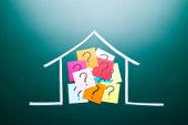 Auf Tafel gemaltes Haus ist voll mit Fragezeichen auf Post-Its