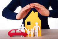 Hände werden schützend über Haus, Auto und Familie aus Papier gehalten