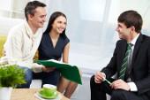 Paar sitzt in einem Büro und werden von jungem Mann beraten