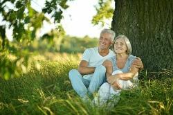 Bild zeigt ein älteres Ehepaar, das an einem Baum sitzt.
