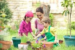 Eine Mutter sitzt mit ihren Kindern in einem schönen Garten.