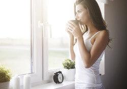 Junge Frau steht Kaffee trinkend am Fenster