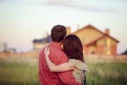 Paar steht gemeinsam vor ihrem Eigenheim