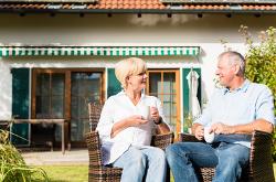 Glückliches älteres Paar sitzt vor dem Eigenheim